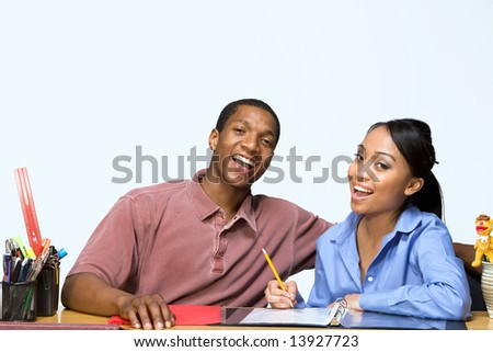 Two Teens are are seated at a desk taking notes and smiling. There are pencils, folders, and paper on the desk. Horizontally framed photograph - stock photo
