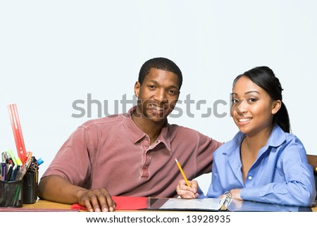 Two Teens are are seated at a desk taking notes and smiling. There are pencils, folders, and paper on the desk. Horizontally framed photgraph - stock photo