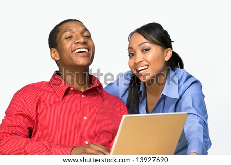 Two Teens are Laughing as they stare ahead and he holds a notebook. Horizontally framed photograph
