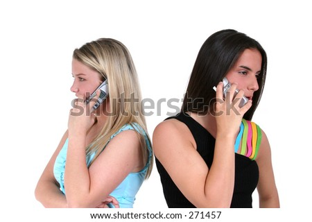 Two teens back to back speaking on cellphones. - stock photo