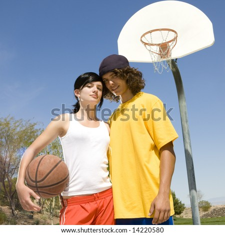 Two teens hang out at a park with a basketball - stock photo