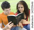 Two teens hang out in a park and read a bible - stock photo