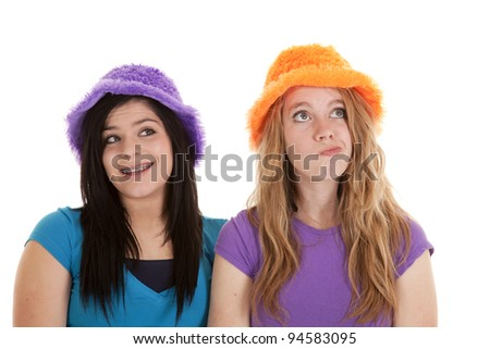 Two teens in their orange an purple fuzzy hats having some fun. - stock photo