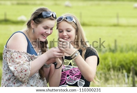Two teens looking and laughing - stock photo