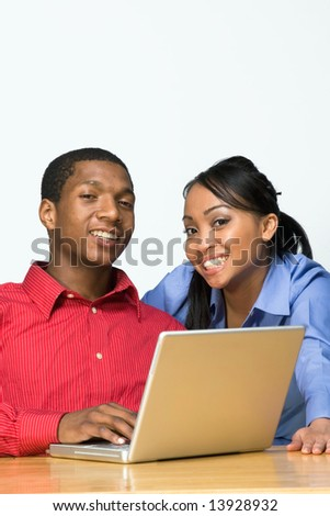 Two Teens looking happy as they smile and he holds a Laptop Computer. Horizontally framed photograph