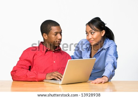 Two Teens looking serious as they stare ahead and he types on a Laptop Computer. Horizontally framed photograph