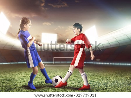 Two teens of school age playing football on stadium - stock photo