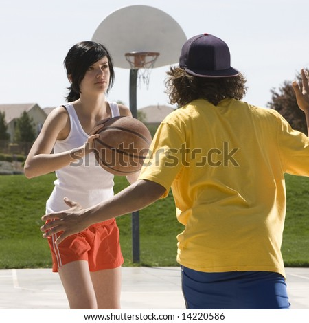 Two teens play basketball at a park - stock photo