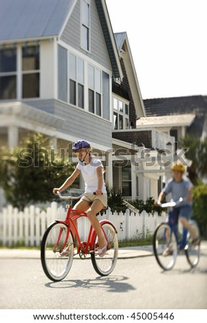 Two teens ride bicycles through a residential neighborhood. Vertical shot. - stock photo