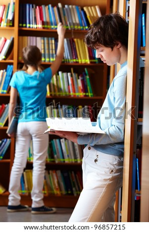Two teens spending time at library looking through books - stock photo