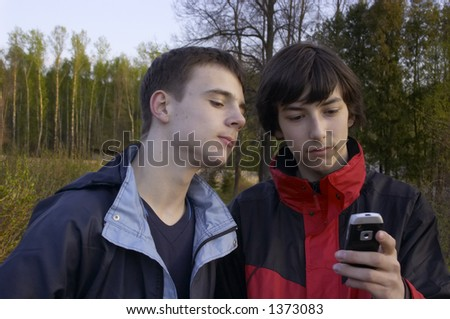 Two teens with cell phone.