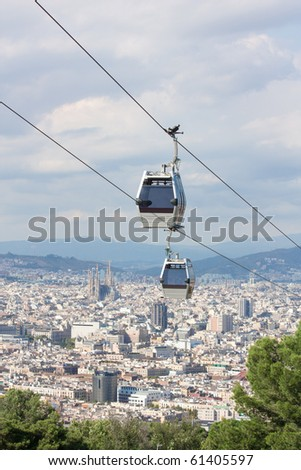 Two teleferics (overhead cable cars) over Barcelona. In this image, taken from Montjuic mountain, we can identify the Sagrada Familia towers, among other distinctive buildings of the city. - stock photo