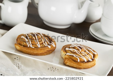 Two tempting cinnamon rolls with tea pot in background - stock photo