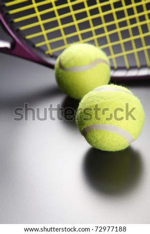 Two tennis balls and a racquet. - stock photo