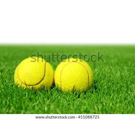 Two tennis balls in the green grass.