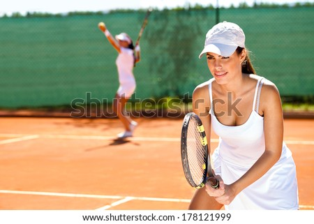 two tennis player playing doubles at tennis court - stock photo