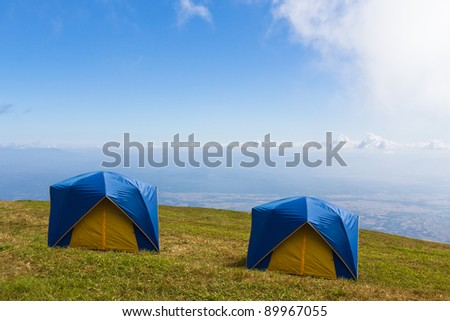 Two Tent on a grass under white clouds and blue sky - stock photo