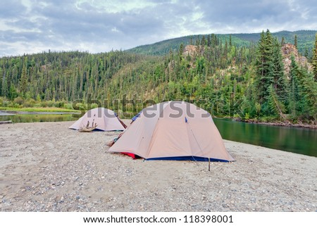Two tents pitched on a sand bar alongside McQuesten River, Yukon Territory, Canada, in remote boreal forest wilderness - stock photo