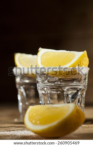 Two tequila shots with lemon and salt on wooden background.