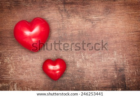 Two Textile pendent hearts on old shabby wooden background - stock photo