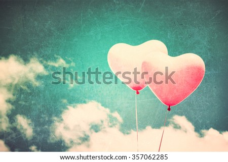 Two textured pink heart shaped balloons flying in a blue sky - stock photo