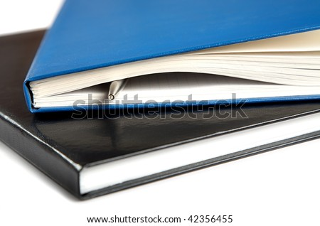Two thick writing-books with a pen on  white background