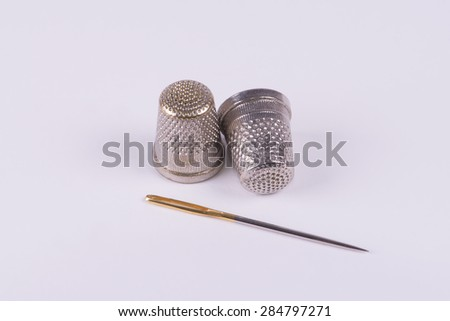 Two thimbles with a needle - stock photo