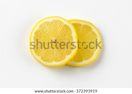 two thin slices of fresh lemon on white background