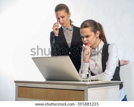 Two thoughtful businesswomen work at the laptop