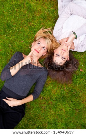 Two thoughtful girls lying in the grass have an smart idea. - stock photo