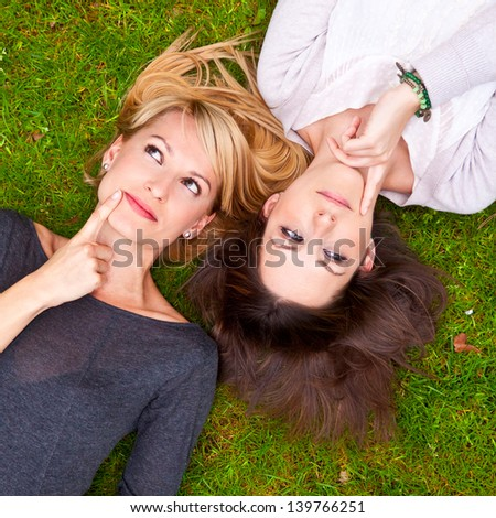 Two thoughtful  girls lying on the meadow. - stock photo