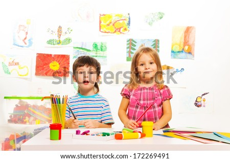 Two three years old kids sitting by the table with paints and brushes - stock photo