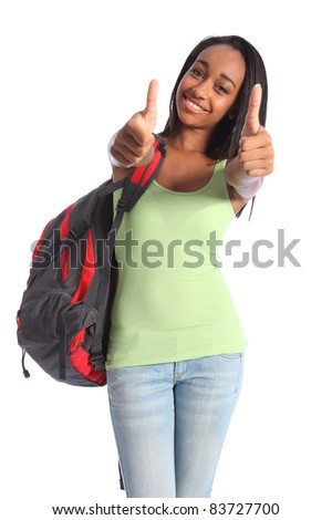 Two thumbs up in double happy success for pretty young African American teenager school girl, with long black hair wearing green t-shirt and red school backpack with beautiful smile. - stock photo