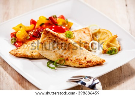 Two tilapia fish fillets on white plate with barbecued vegetables - stock photo