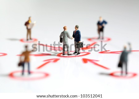 Two tiny miniature businessmen shake hands in the centre of a networking web surrounded by linked colleagues offering support and teamwork in business - stock photo