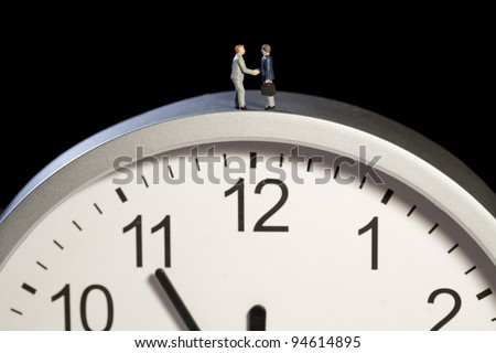 Two tiny model figures of businessmen shaking hands on top of a clock showing the time as five minutes to twelve, horizontal - stock photo
