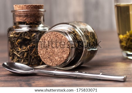 Two tiny tea jars and a spoon