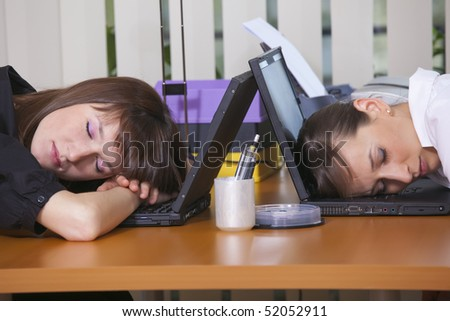 two tired business women sleeping on laptops - stock photo