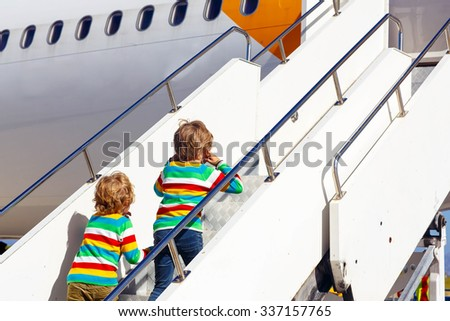 Two tired little sibling kids boys at the airport, traveling together. Upset children waiting and playing with tablet pc. Canceled flight due to pilot strike. Selective focus on one child - stock photo