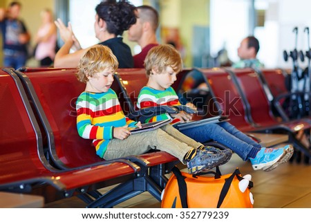 Two tired little sibling kids boys at the airport, traveling together. Upset children waiting and playing with tablet pc. Canceled flight due to pilot strike. - stock photo