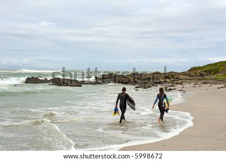Two tired surfers walk on beach. Shot on West Coast, between Grotto Bay nature reserve and Silwerstroomstrand, Western Cape, South Africa. - stock photo