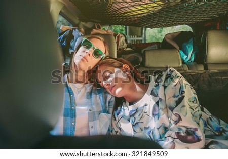 Two tired young women friends sleeping together in the rear seat of car. Female friendship and leisure time concept. - stock photo