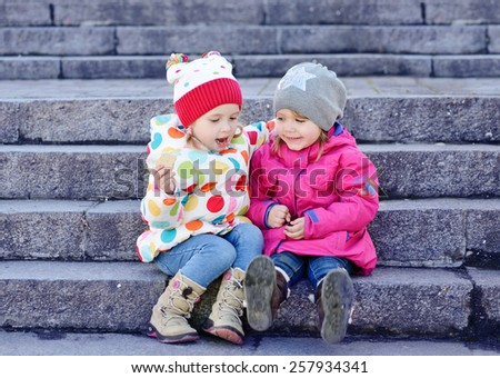 two toddler friends sitting on the stairs - stock photo