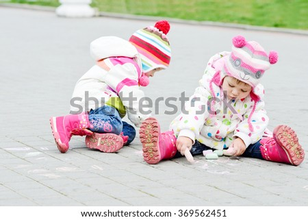 two toddler girls are drawing with chalk
