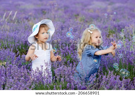 two toddler girls catching soap bubbles in lavender field - stock photo