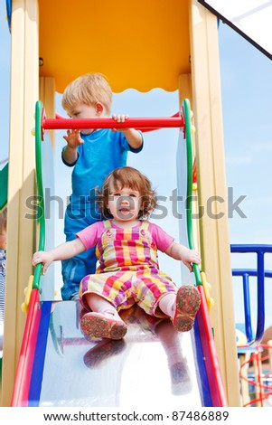 Two toddlers on a chute