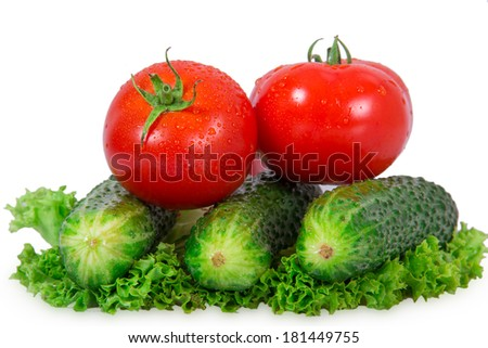 Two tomatoes and three cucumber lie on lettuce leaf on a white background - stock photo