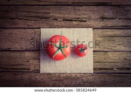 Two tomatoes of two different sizes on a rough wooden table - stock photo