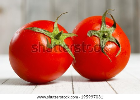 two tomatoes on white wooden table - stock photo