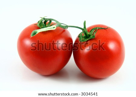 two tomatos with a bit of shadow isolated on white - stock photo